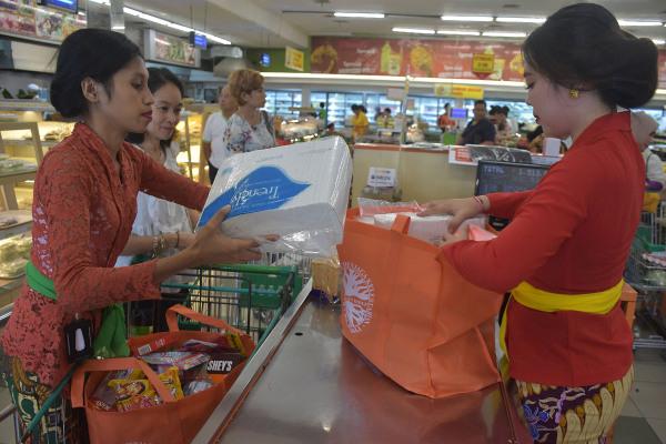 Karyawan swalayan mengemas barang belanjaan konsumen dengan tas ramah lingkungan di pusat perbelajaan di Denpasar, Bali, Kamis (3/1/2019). - ANTARA/Nyoman Hendra Wibowo