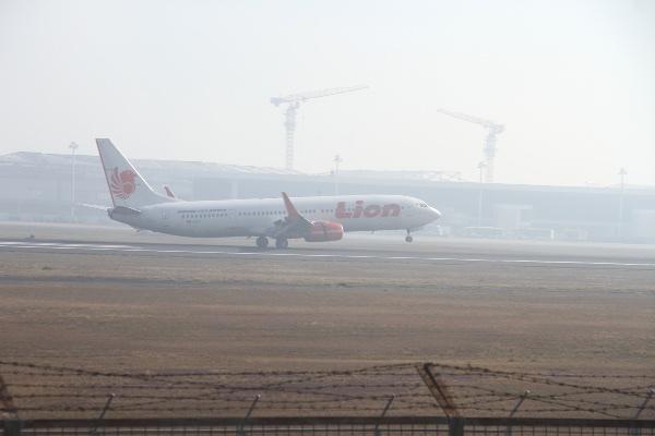 Pesawat komersial mendarat di Bandara Syamsudin Noor yang diselimuti kabut asap di Banjarbaru, Kalimantan Selatan, Rabu (11/9/2019). - ANTARA FOTO/Bayu Pratama S