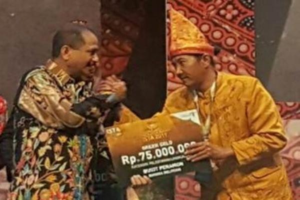 Menteri Pariwisata Republik Indonesia (RI) Arief Yahya (kiri) menyerahkan simbolis penghargaan Green Gold kategori Pelestarian Lingkungan kepada Ketua Komunitas Arsel sekaligus penanggung jawab Desa Binaan Bukit Peramun Adie Darmawan (kanan) dalam ajang ISTA - Indonesian Sustainable Tourism Awards 2019 yang digelar pada Kamis (26 - 9) di Jakarta