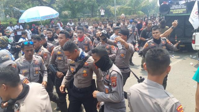 Puluhan aparat keamanan berjoget gembira di sekitar mobil komando massa buruh di DPR. Aksi kali ini berlangsung kondusif dengan tetap dikawal aparat. Rayful Mudassir - Bisnis Indonesia