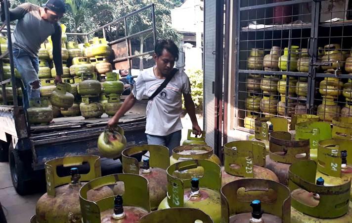 Ilustrasi-Pekerja membongkar tabung gas LPG 3kg di salah satu agen penjualan - Bisnis/Endang Muchtar