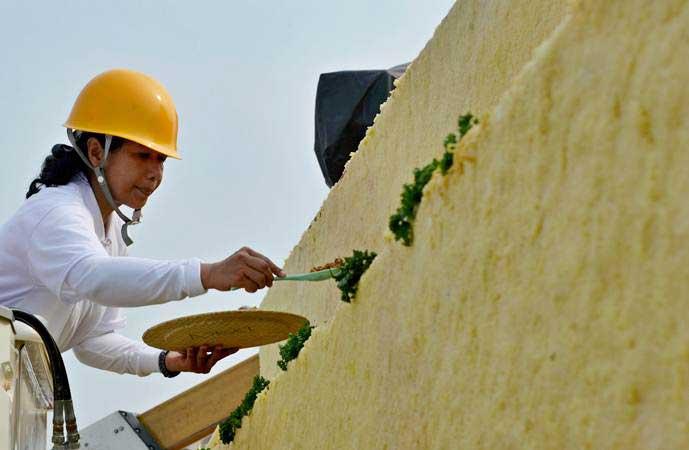 Menteri BUMN Rini Soemarno mengambil lauk tumpeng nasi kuning setinggi 13 meter dari atas kendaraan