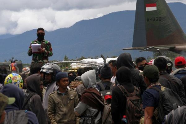 Prajurit TNI mendata warga yang akan meninggalkan Wamena menggunakan pesawat Hercules milik TNI AU di Bandara Wamena, Jayawijaya, Papua, Selasa (1/10/2019). Pascakerusuhan yang mengakibatkan 33 orang meninggal dunia pada 23 September 2019, jumlah warga Wamena yang dievakuasi menggunakan pesawat Hercules dari Wamena ke Jayapura mencapai 6.520 orang. - Antara/Iwan Adisaputra