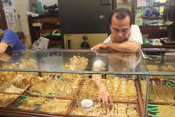 Seorang pegawai toko emas di Pasar Sentral Antasari Banjarmasin, Kalimantan Selatan sedang menyusun emas perhiasan Senin (1/10/2018). - Bisnis/Arief Rahman