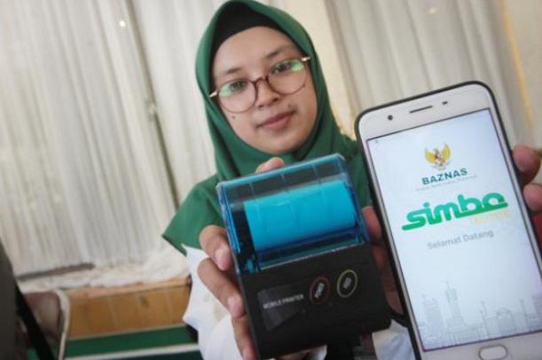 Petugas Badan Amil Zakat Nasional (Baznas) menunjukkan aplikasi zakat - Bisnis