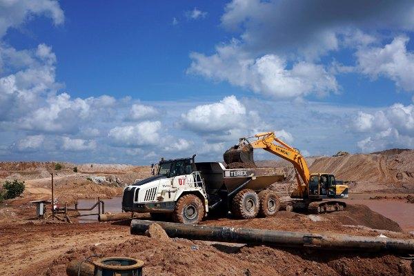 Ekskavator mengangkut tanah ke truk di tambang terbuka milik PT Timah Tbk. di Pemali, Bangka, Indonesia, Kamis (25/7/2019). - Reuters/Fransiska Nangoy