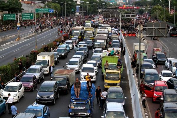 Antrean kendaraan terjebak di tol dalam kota akibat aksi demonstrasi di sekitar Gedung DPR di Jakarta pada Senin (30/9). Dinamika politik dan keamanan pada pertengahan hingga akhir September lalu dianggap menjadi disinsentif di sektor keuangan. - Bisnis/Arief Hermawan