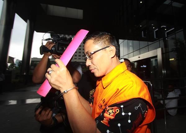 Bupati Cirebon nonaktif Sunjaya Purwadisastra menutupi wajahnya ketika keluar usai menjalani pemeriksaan di Gedung KPK, Jakarta, Senin (21/1/2019). - ANTARA/Reno Esnir