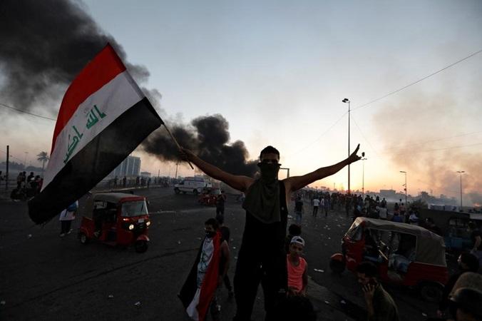 Seorang demonstran memegang bendera Irak pada saat protes anti-pemerintah yang berubah menjadi kekerasan, di Baghdad, Irak, 5 Oktober 2019. - REUTERS/Thaier Al/Sudani