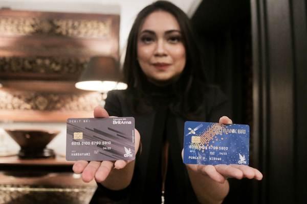 Karyawati memperlihatkan kartu debit PT Bank Rakyat Indonesia Tbk. berlogo Gerbang Pembayaran Nasional (GPN). - JIBI/Felix Jody Kinarwan