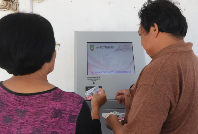 Pedagang pasar Jongke Laweyan, Solo membayar retribusi melalui kios E-Retribusi Bank Jateng di pintu masuk pasar, Rabu (31/10/2019). Penerapan E-Retribusi tersebut memudahkan para pedagang dalam membayar retribusi pasar dengan cara aman dan nyaman. - JIBI/Sunaryo Haryo Bayu