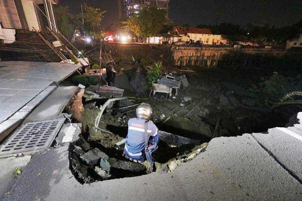 Petugas memeriksa tanah yang ambles di Kawasan Gubeng Surabaya, Jawa Timur, Selasa (18/12/2018). - ANTARA/Didik Suhartono