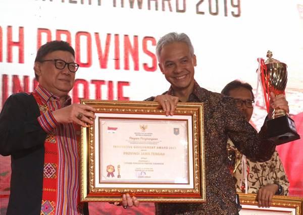 Menteri Dalam Negeri, Tjahjo Kumolo (kiri) memberikan penghargaanprovinsi paling inovatif tahun 2019 dalam Innovative Government Award 3 kepada Gubernur Jawa Tengah Ganjar Pranowo. - Istimewa