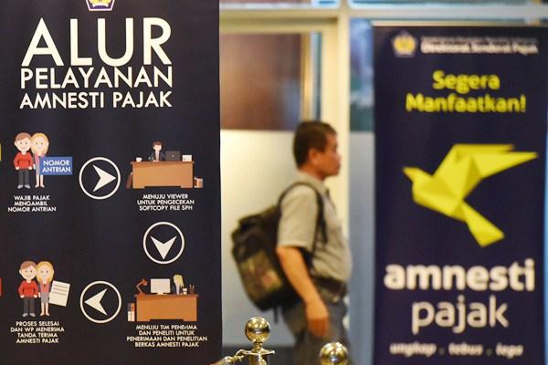 Wajib pajak berjalan menuju bilik tax amnesty di Kantor Pusat Ditjen Pajak, Jakarta, Rabu (29/3). - Antara/Akbar Nugroho Gumay