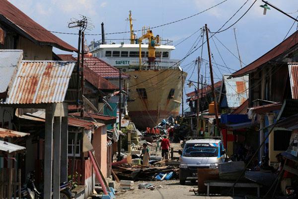 Warga berjalan di depan rumah mereka yang dihantam gempa dan tsunami di Desa Wani, Donggala, Sulawesi Tengah, di dekat kapal feri KM Sabuk Nusantara 39 yang terangkat dari lautan ke daratan. Gempa dan tsunami terjadi pada Jumat (28/9/2018) menjelang malam, foto diambil pada Selasa (2/10/2018). - Reuters/Beawiharta