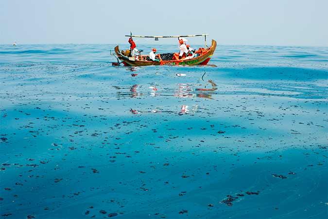 Petugas mengumpulkan tumpahan minyak mentah yang tercecer di Laut Utara Karawang, Jawa Barat. Foto - Antara