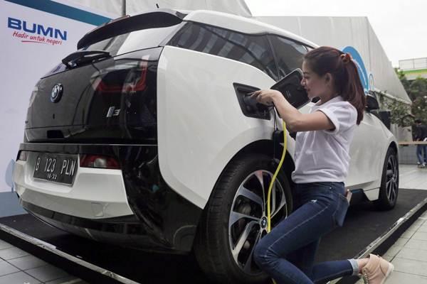Model memperagakan cara pengisian bahan bakar listrik ke mobil BMW I3 melalui Stasiun Penyedia Listrik Umum (SPLU) dalam acara LIKE (Learning, Inovation, Knowledge Exibition) PLN di Jakarta, Selasa (17/10). - JIBI