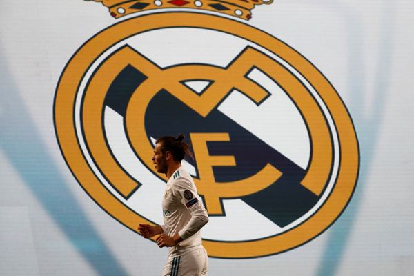 Gareth Bale berlatar belakang logo Real Madrid. - Reuters