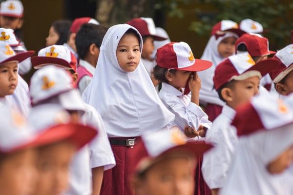 Seorang anak pencari suaka (tengah) yang kini duduk di kelas 1 SDN 159 mengikuti upacara penaikan bendera di Kota Pekanbaru, Riau, Senin (7/10/2019). Sebanyak 81 anak pencari suaka berstatus pengungsi luar negeri pada Oktober 2019 mulai bersekolah di SD negeri di Pekanbaru, dan wajib ikut serta dalam kegiatan upacara bendera untuk melatih kedisiplinan dan cinta tanah air tempat mereka tinggal. - Antara/FB Anggoro