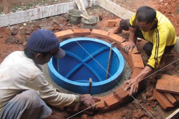 Ilustrasi: Pekerja terlatih sedang memasang cetakan fiber untuk membuat tangki septik layak. - iuwash.or.id