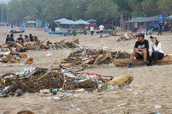 Wisatawan duduk di antara tumpukan sampah di kawasan Pantai Kuta, Badung, Bali, Selasa (1/1/2019). - ANTARA/Nyoman Hendra Wibowo