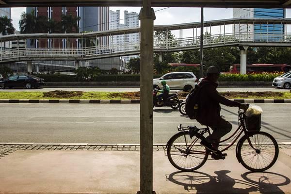 Warga melintas di jalur pedestrian di kawasan Jalan Sudirman, Jakarta, Rabu (14/3). - ANTARA FOTO/Galih Pradipta