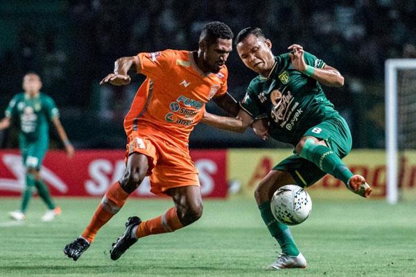 Pemain sayap Persebaya Surabaya Oktafianus Fernando (kanan) berusaha mempertahankan bola yang hendak direbut oleh gelandang Borneo FC Makarius Fredik Suruan. Skor akhir 0 - 0. - Persebaya.id