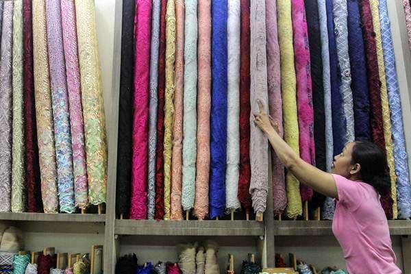 Penjual bahan kain menata dagangannya di Pusat Grosir Tanah Abang, Jakarta, Jumat (14/9/2018). - ANTARA/Muhammad Adimaja