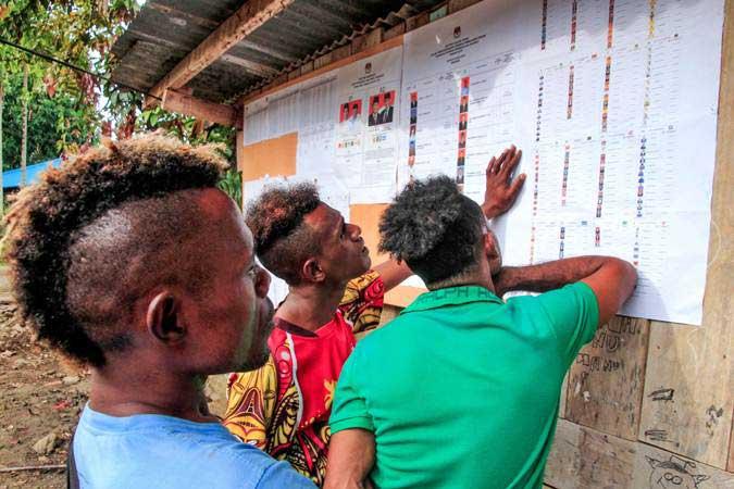 Warga mengamati daftar calon anggota legislatif pada Pemilu 2019 di TPS Kampung Wahno, Distrik Abepura, Jayapura, Papua, Selasa (17/4/2019). - ANTARA/Gusti Tanati