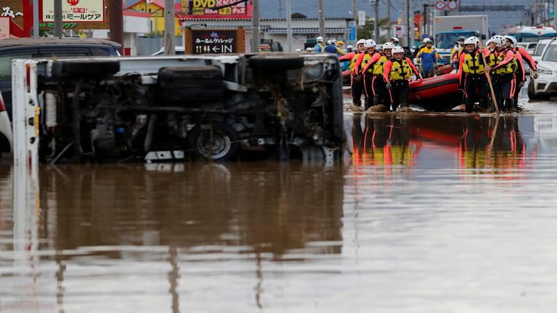 Petugas penyelamat membawa sampan karet melewati mobil yang terbalik ketika mencari korban di daerah banjir setelah Topan Hagibis, yang menyebabkan banjir parah di Sungai Chikuma di Prefektur Nagano, Jepang, 14 Oktober 2019. - Reuters