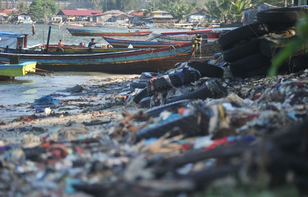 Nelayan menepikan perahunya di pantai yang penuh sampah, di pantai Gaung, Padang, Sumatera Barat, Selasa (30/7/2019). Sampah rumah tangga, seperti pakaian bekas dan plastik berserakan di pantai yang berada di kawasan permukiman pesisir tersebut. - Antara / Iggoy el Fitra.