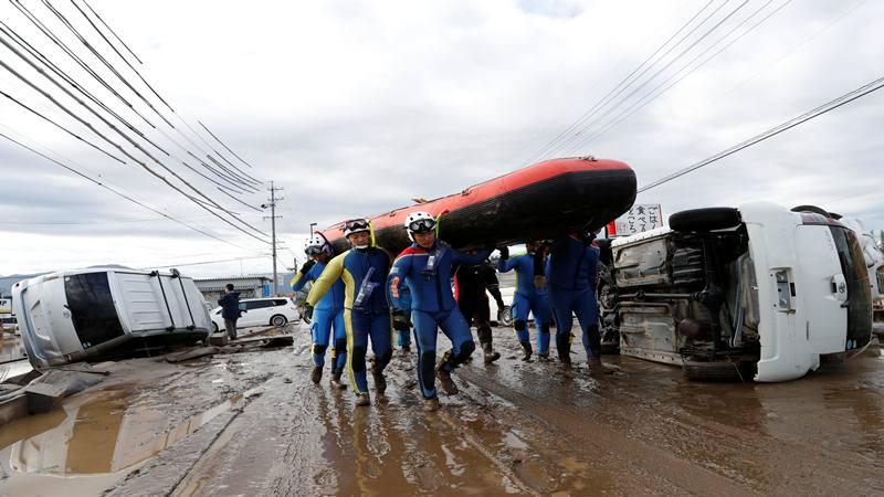 Petugas penyelamat membawa perahu karet ketika mereka mencari daerah banjir setelah Topan Hagibis yang menyebabkan banjir parah di Sungai Chikuma di Prefektur Nagano, Jepang, 14 Oktober 2019. - Reuters