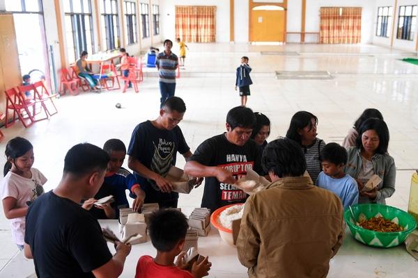Sejumlah warga antre mengambil makanan di posko pengungsian Tongkonan Toraja, Kota Wamena, Kabupaten Jayawijaya, Papua, Sabtu (12/10/2019). Sebanyak 154 orang yang masih berada di posko pengungsian tersebut dikarenakan rumahnya yang habis terbakar pascaaksi unjuk rasa yang berujung anarkis pada 23 September 2019. - Antara/M Risyal Hidayat