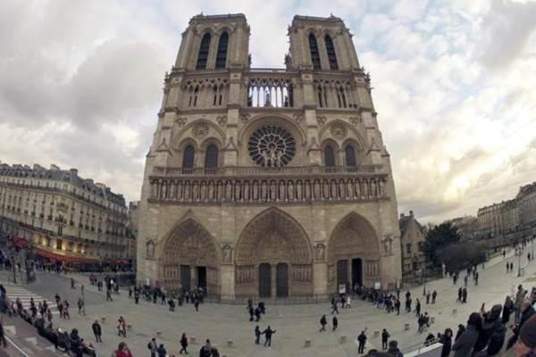 Masyarakat berjalan melewati pintu masuk ke Katedral Notre Dame di Paris 8 Februari 2013. - REUTERS/Charles Platiau