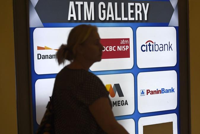 Warga melintasi galeri anjungan tunai mandiri (ATM) di Kebayoran Lama, Jakarta, Senin (5/8/2019). - ANTARA/Aditya Pradana Putra.