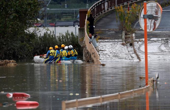 Seorang pria berbicara dengan petugas penyelamat setelah Topan Hagibis, yang menyebabkan banjir parah di Sungai Chikuma di Nagano, Prefektur Nagano, Jepang, 14 Oktober 2019. - REUTERS/Kim Kyung/Hoon