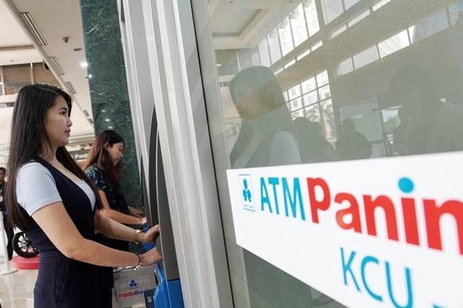 Nasabah melakukan transaksi di mesin anjungan tunai mandiri (ATM) Bank Panin, di Jakarta, Jumat (5/7/2019). - Bisnis/Himawan L Nugraha