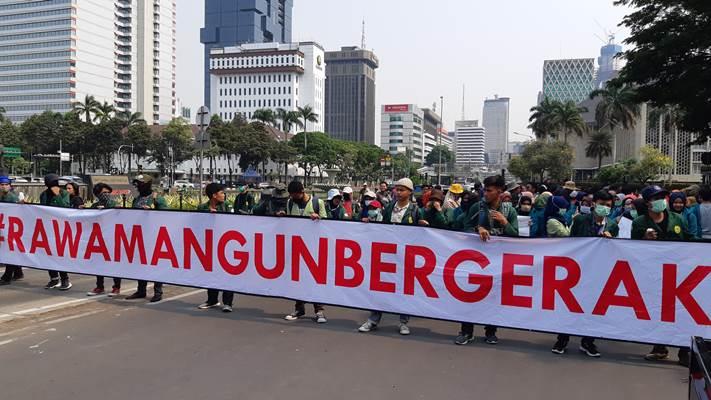 Mahasiswa membentangkan spanduk saat menggelar aksi di dekat Patung Kuda, Thamrin, Jakarta Pusat - Bisnis/Rayful Mudassir