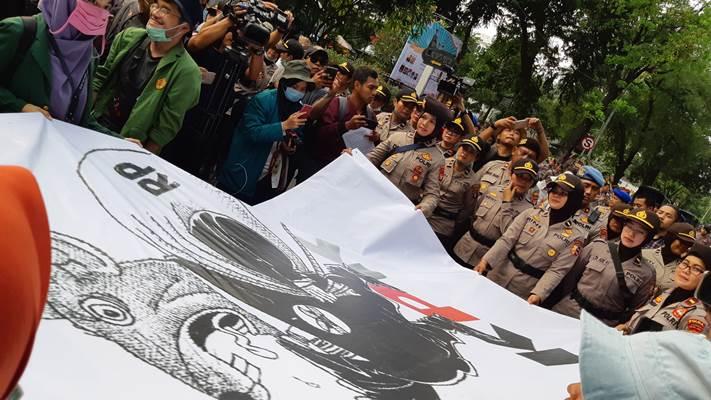 Mahasiswa menyerahkan poster bergambar tikus berdasi kepada anggota Polwan - Bisnis/Rayful Mudassir