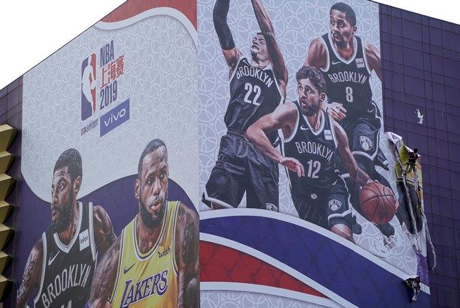Seorang pekerja melepas iklan raksasa NBA China Games dari sebuah gedung di Shanghai, China 9 Oktober 2019. - REUTERS/Aly Song
