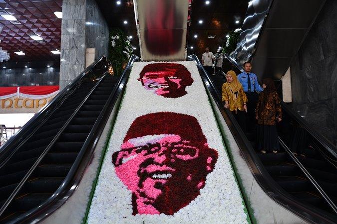 Petugas menuruni eskalator di samping hiasan bunga bergambar Presiden dan Wakil Presiden terpilih Joko Widodo dan Ma'ruf Amin disela gladi bersih pelantikan di Kompleks Parlemen, Senayan, Jakarta, Sabtu (19/10/2019). - ANTARA/Sigid Kurniawan