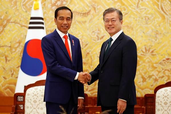 Presiden Joko Widodo (kiri) berjabat tangan dengan Presiden Korea Selatan Moon Jae-in di the Presidential Blue House, Korea Selatan, Senin (10/9/2018). - Reuters/Kim Hong/Ji