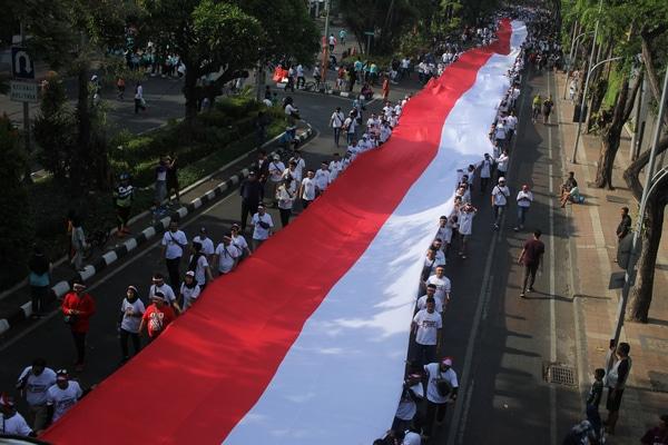 Polisi dan warga membawa Bendera Merah Putih saat Parade Merah Putih Indonesia Damai di Jalan Darmo, Surabaya, Jawa Timur, Minggu (20/10/2019). Kegiatan dengan kirab Bendera Merah Putih sepanjang 210 meter itu digelar untuk menjaga dan merawat kebhinekaan yang ada di Indonesia. - Antara/Didik Suhartonos