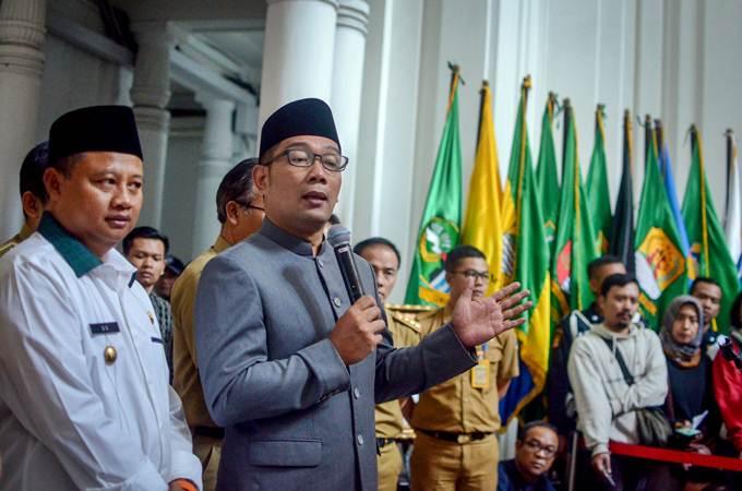Gubernur Jawa Barat Ridwan Kamil (kedua kiri) didampingi Wakil Gubernur Uu Ruzhanul Ulum (kiri) memberikan keterangan kepada awak media di Gedung Sate, Bandung, Selasa (30/7/2019). - ANTARA/Raisan Al Farisi