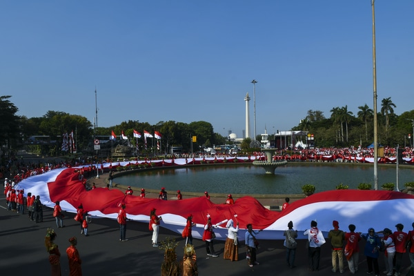 Relawan mengibarkan bendera merah putih saat mengikuti pesta rakyat di kawasan Patung Kuda, Jakarta, Minggu (20/10/2019). Pesta rakyat tersebut untuk menyambut Presiden dan Wakil Presiden periode 2019-2024 Joko Widodo-Ma'ruf Amin. - Antara/Galih Pradipta