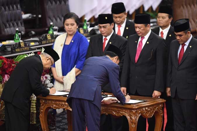 Presiden Joko Widodo (kedua kiri) dan Wapres Ma'ruf Amin membubuhkan tanda tangan disaksikan para pimpinan MPR saat upacara pelantikan presiden dan wakil presiden periode 2019-2024 di Gedung Nusantara, kompleks Parlemen, Senayan, Jakarta. Antara - Akbar Nugroho Gumay