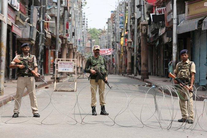 Personel keamanan India berjaga di sepanjang jalan sepi selama pembatasan di Jammu, 5 Agustus 2019. - REUTERS/Mukesh Gupta