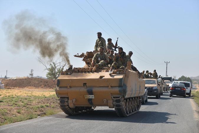 Anggota Tentara Nasional Suriah, yang dikenal sebagai Free Syrian Army, berkendara untuk menyeberang ke Suriah dekat kota perbatasan Turki Ceylanpinar di provinsi Sanliurfa, Turki, 10 Oktober 2019. - REUTERS/Stringer.