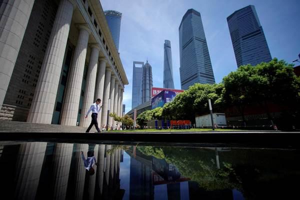Seorang pria berjalan di Lujiazui, distrik finansial di Pudong, Shanghai, China, 17 Juli 2017. - REUTERS/Aly Song