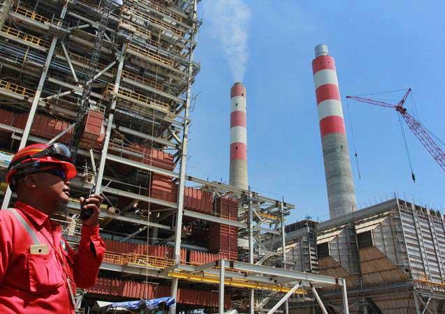 Pekerja berkomunikasi dengan operator alat berat pada proyek pembangunan Pembangkit Listrik Tenaga Uap (PLTU) Lontar Extension 1x315 MW di Desa Lontar, Tangerang, Banten, Jumat (29/3/2019). - ANTARA/Muhammad Iqbal